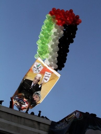 Balloons lift up a giant poster of Mahmoud Abbas and Yasser Arafat at the Fatah rally in Gaza City on Friday. Demonstrators, many of them women and children waved Palestinian and Fatah flags and carried pictures of Abbas, an AFP correspondent reported (photo via Yahoo)