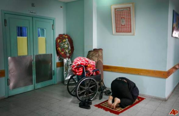 A Palestinian man prays next to a wheelchair at the Shifa hospital in Gaza City, Monday, Jan. 26, 2009. Israel launched its 22-day offensive to try to halt Hamas rocket fire on southern Israel. The assault killed 1,285 Palestinians, more than half of them civilians, the Palestinian Center for Human Rights counted. Thirteen Israelis, including three civilians, were also killed during the fighting, Israel said. (AP Photo/Anja Niedringhaus)