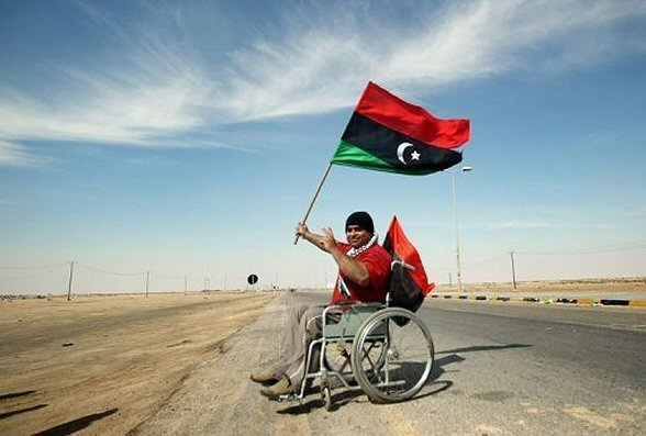 Wheelchair-bound Palestinian Motassem Hassan raises Libya's independence flag as he visits rebels at the western gate of the strategic town of Ajdabiya on April 19, 2011.