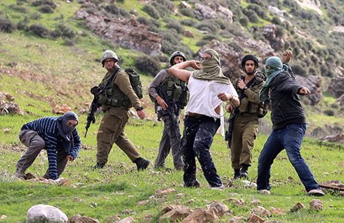 Masked Israeli settlers protected by the Israeli army