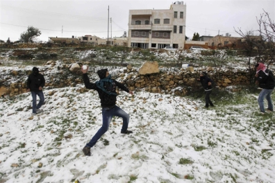 Palestinians play with snow during a snow storm in the West Bank village of Halhul near Hebron January 9, 2013. At least 17 people have died due to a winter storm in Lebanon, Jordan, Turkey, Israel and the Palestinian territories. Meteorological agencies in Israel and Lebanon both called it the worst storm in 20 years. REUTERS/Ammar Awad