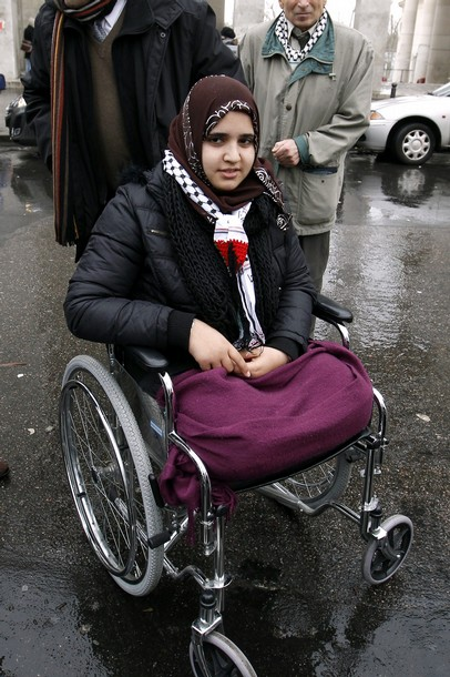 Jamila Al Habash poses on her wheelchair after visiting an exhibition by German photographer Kai Wiedenhöfer entitled 'Gaza 2010' at the Paris Modern Art Museum, on December 4, 2010. The photographs of the exhibition feature war damages and Palestinian victims after the Cast Lead Operation in 2008-2009 with notably a portrait of Jamila Al Habash. Jamila was 16 when she lost both her legs in Operation Cast Lead. She's in France for surgical treatment. Photo by Getty