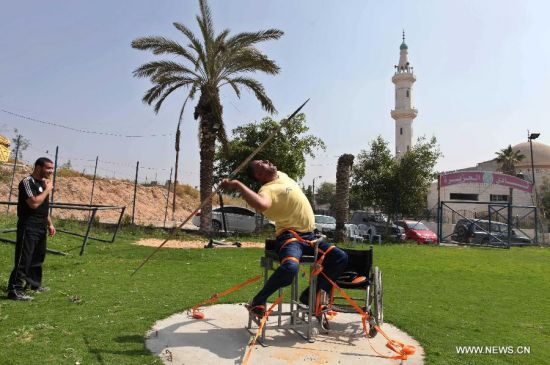 Khamis Zakout, a Palestinian wheelchair athlete throws a javelin during a training session in Gaza City, on April 9, 2012. Zakout is preparing himself for the upcoming London Paralympics. (Xinhua/Wissam Nassar)