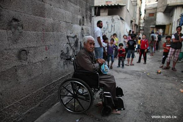 "An old and disabled Palestinian man is seen sitting in a wheelchair in the Al-Shati refugee camp in Gaza City on May 10, 2012. On May 15 every year, Palestinians across the world mark ""Nakba day"" or catastrophe, an annual commemoration for the Palestinian people's displacement that accompanied the creation of the Israeli state in 1948. (Xinhua/Wissam Nassar)"