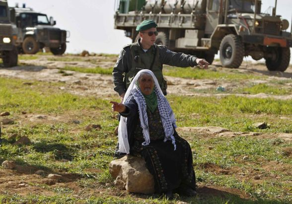 An Israeli soldier orders a Palestinian woman to leave after the Israeli army banned them from setting up a encampment in the West Bank village of Al-Tiwaneh south of the West Bank town of Hebron February 9, 2013. The Israeli military prevented Palestinians from setting up an encampment on Saturday to protest at Jewish settlement expansion in the occupied West Bank, land where they seek statehood.REUTERS/ Ammar Awad