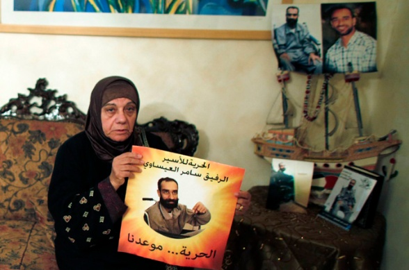 Layla al-Issawi holds a placard depicting her son Samer, on hunger strike for over 200 days (Reuters)