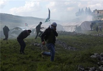 A Palestinian activist runs from teargas after Israeli forces evacuate a protest camp in the West Bank village of Burin, south of Nablus,  Feb. 2, 2013. (Reuters/Mohamad Torokman)