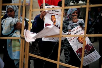 A Palestinian woman holds her baby during a protest in Gaza City calling for the release of Palestinian prisoners from Israeli jails, Feb. 5, 2013. (Reuters/Suhaib Salem)