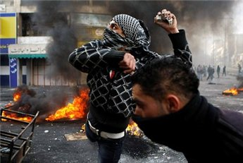 A protester throws stones during clashes with Israeli soldiers in the city of Hebron February 25, 2013 following the funeral of Palestinian  prisoner Arafat Jaradat. (Reuters/Mussa Qawasma)