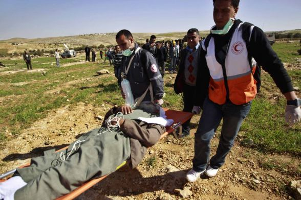 A Palestinian medic evacuates an injured Palestinian during a protest after the Israeli army banned them from setting up a encampment in the West Bank village of Al-Tiwaneh south of the West Bank town of Hebron February 9, 2013. The Israeli military prevented Palestinians from setting up an encampment on Saturday to protest at Jewish settlement expansion in the occupied West Bank, land where they seek statehood. REUTERS/ Ammar Awad