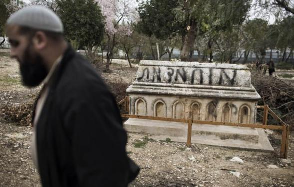 "A Muslim man walks past a tomb vandalised with spray paint with a graffiti reading in Hebrew: ""Mohammed (prophet) is Dead"" at the Mamun Allah cemetery, an old Muslim cemetery in Jerusalem on February 14, 2013. (Photo: AFP - Marco Longari)"