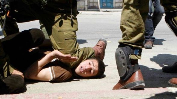 An Israeli soldier presses his knee into the neck of a Palestinian youth in the West Bank city of al-Khalil (Hebron) on May 11, 2012.