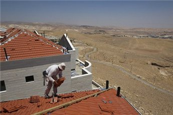A laborer works atop a roof at a construction site in the settlement of  Maale Adumim in the West Bank. (Reuters/Ronen Zvulun, File)
