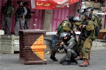 An Israeli border policeman and soldiers take position as a stone  thrown by protesters is seen above a crate during clashes in the  West Bank city of Hebron March 1, 2013. (Reuters/Ammar Awad)