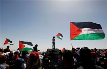 Activists hold Palestinian flags at a rally marking Land Day in the  West Bank village of al-Tuwani, south of Hebron March 29, 2013.  (Reuters/Ammar Awad)