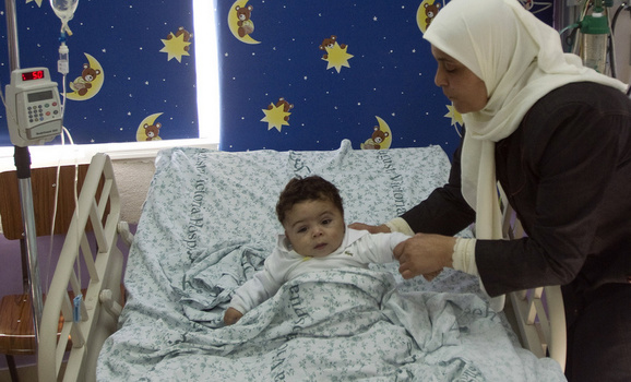 A Palestinian women lifts her son in the paediatric ward of Augusta Victoria Hospital in East Jerusalem