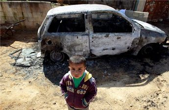 A boy stands next to a car burnt by settlers in Nablus.