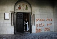 A monk stands next to graffiti sprayed on a wall at the entrance to  the Latrun Monastery near Jerusalem September 4, 2012. (Reuters/Baz Ratner)