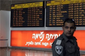 An Israeli border policeman stands next to the international arrivals  board at Ben Gurion airport. (AFP/David Buimovitch, File)