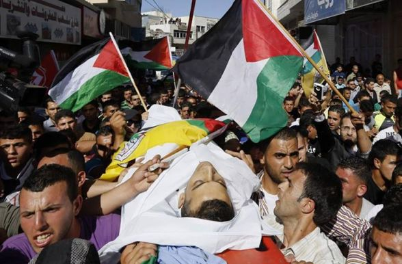 Palestinians carry the body of martyr Moataz sharawneh during his funeral in the West Bank village of Dura, near Hebron July 2, 2013. Lens/Ammar Awad