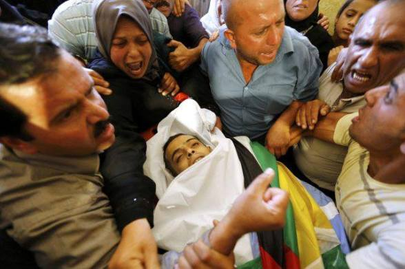 Sihan the mother of Martyr Moataz Sharawneh, mourns near her son's body during his funeral in the West Bank village of Dura, near Hebron July 2, 20 Lens/Ammar Awad