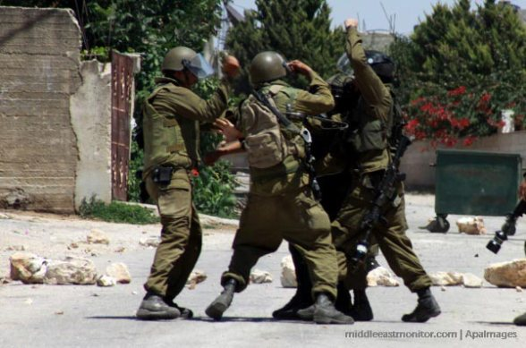Israeli soldiers beating a Palestinian media reporter during a weekly protest at Kufr Qaddum village near the West Bank city of Nablus (June 2013)