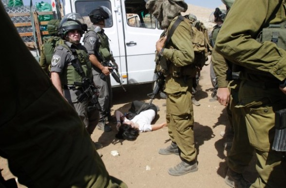 French diplomat Marion Castaing lays on the ground after Israeli soldiers carried her out of her truck containing emergency aid, in the West Bank herding community of Khirbet al-Makhul, in the Jordan Valley September 20, 2013. Israeli soldiers manhandled European diplomats, including Castaing, on Friday and seized the truck full of tents and emergency aid they had been trying to deliver to Palestinians whose homes were demolished earlier this week. REUTERS/Abed Omar Qusini