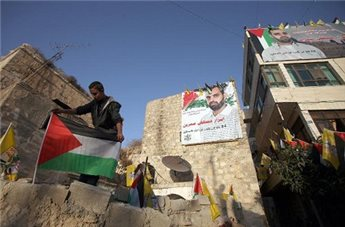 Relatives of prisoner Mustafa Samreen, hang his image on the walls of homes in his neighborhood of al-Bireh, in the Israeli occupied West Bank, on October 29, 2013, prior to his release from 24 years in an Israeli jail.(AFP/Abbas Momani)