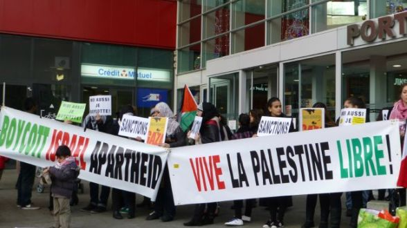 File photo shows French activists holding a demonstration to demand boycotting Israeli goods.