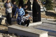 Muslims visit the graves of their relatives on the first day of Eid al-Adha in Jalazoun