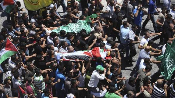 Palestinians carry the bodies of Khaled Azmi and Tayyeb Shehada, whom medics said were killed during clashes with Israeli troops on Friday, during their funeral in the West Bank town of Hawara near Nablus July 26, 2014 . Photo by REUTERS/Abed Omar Qusini