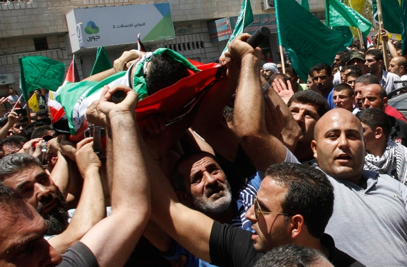 Palestinians carry the bodies of Khaled Azmi and Tayyeb Shehada, whom medics said were killed during clashes with Israeli troops on Friday, during their funeral in the West Bank town of Hawara near Nablus July 26, 2014 . Medics said eight Palestinians were killed in incidents near the West Bank cities of Nablus and Hebron on Friday -- the sort of death toll reminiscent of previous uprisings against Israel's prolonged military rule there, which shows no sign of ending. The Gaza turmoil has stoked tensions amongst Palestinians in the occupied West Bank. REUTERS/Abed Omar Qusini