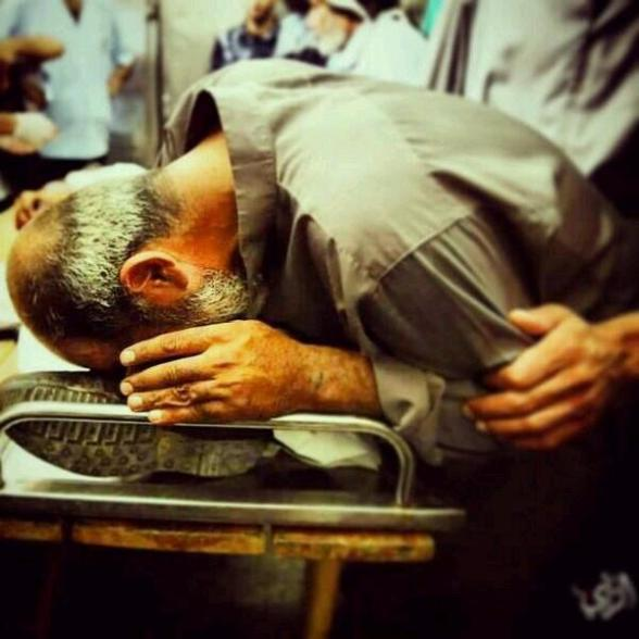 Martyr journalist Khaled Hamad's father kisses his foot & say the last goodbye. via  ‏@HindSaeed1
