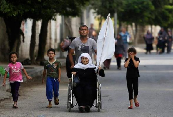 Photo via @HaniSiliman : Old women is raising a white flag and is feeling with her family away from Al-Shojai'ya area east Gaza