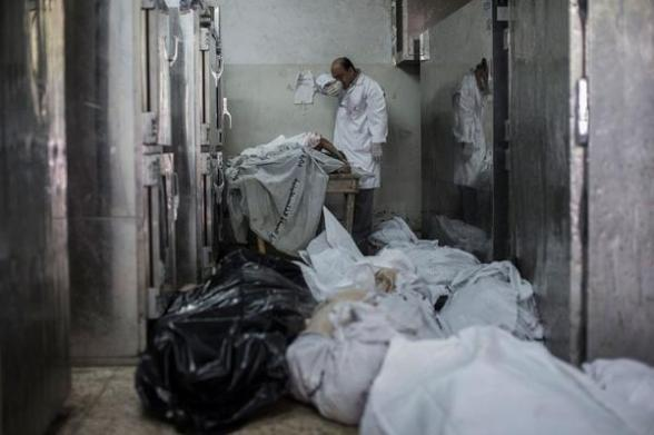 A doctor cries while standing next to a table with the bodies of four dead children in Shifa hospital in #Gaza - Photovia  @m_househ