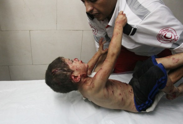 Palestinian medic tries to comfort a wounded boy at Shifa hospital in Gaza City, northern Gaza Strip,