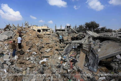 Palestinians inspect destroyed houses as they returning to their homes in the Al-Shejaia neighbourhood of Gaza City