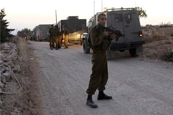 Israeli soldiers stand guard next to their vehicles on June 30, 2014 as they block the northern entrance of the village of Halhul, near the West Bank town of Hebron, after the bodies of the three Israeli teenagers were found (AFP Hazem Bader)