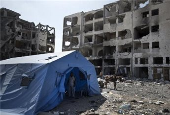 A tent is pitched in front of the destroyed Nada Towers as Palestinians return to the area to inspect what remains of their homes, Aug. 11, 2014, in Beit Lahia in the northern Gaza Strip (AFP Mahmud Hams)