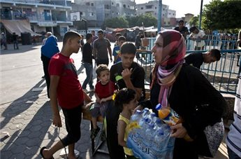 A Palestinian woman displaced from her home when fighting broke out between Israel and Hamas militants over four weeks ago, carries water bottles given to her as food handouts on Aug. 16, 2014 at a United Nations school in Jabalia (AFP Roberto Schmidt)