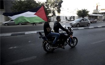 Palestinians carry the national flag as they ride through the streets of Gaza to celebrate the agreement to form a unity government on April 23, 2014 (AFP/File Mahmud Hams)