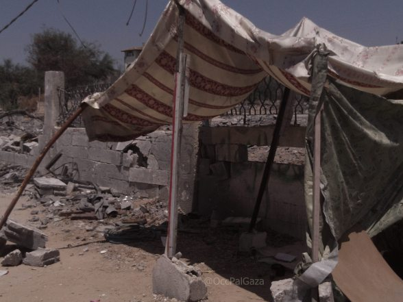 Makeshift tent in front of destroyed home