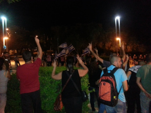 Palestinians raise their hands in victory sign against right wing demo in Haifa