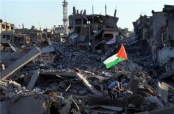 Residents walk through the rubble of their destroyed home as a Palestinian flag flutters in the wind, in the devastated neighborhood of Shujaiyya in Gaza City on Aug. 7, 2014 (AFP/Roberto Schmidt)